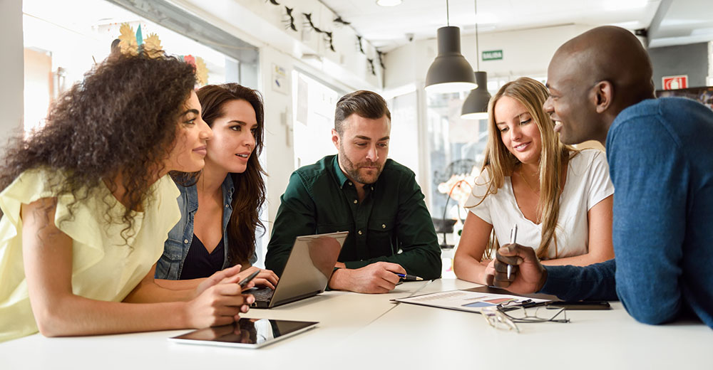 Five young people studying with laptop and tablet computers on white desk. Beautiful girls and guys working toghether wearing casual clothes. Multi-ethnic group smiling.